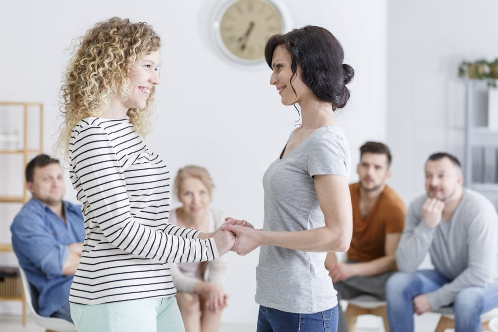 Happy mother and daughter standing and holding hands in family counseling in a bright psychologist's office