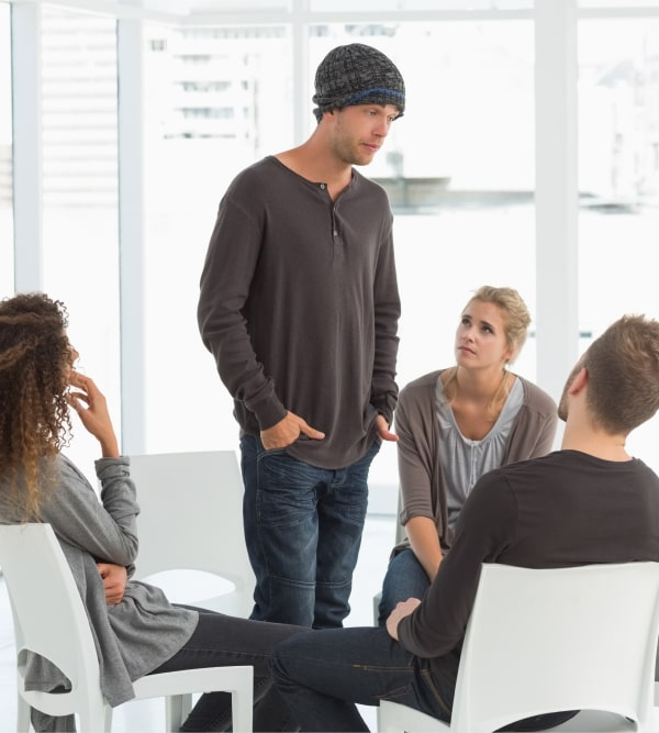 man talking in group therapy for addiction